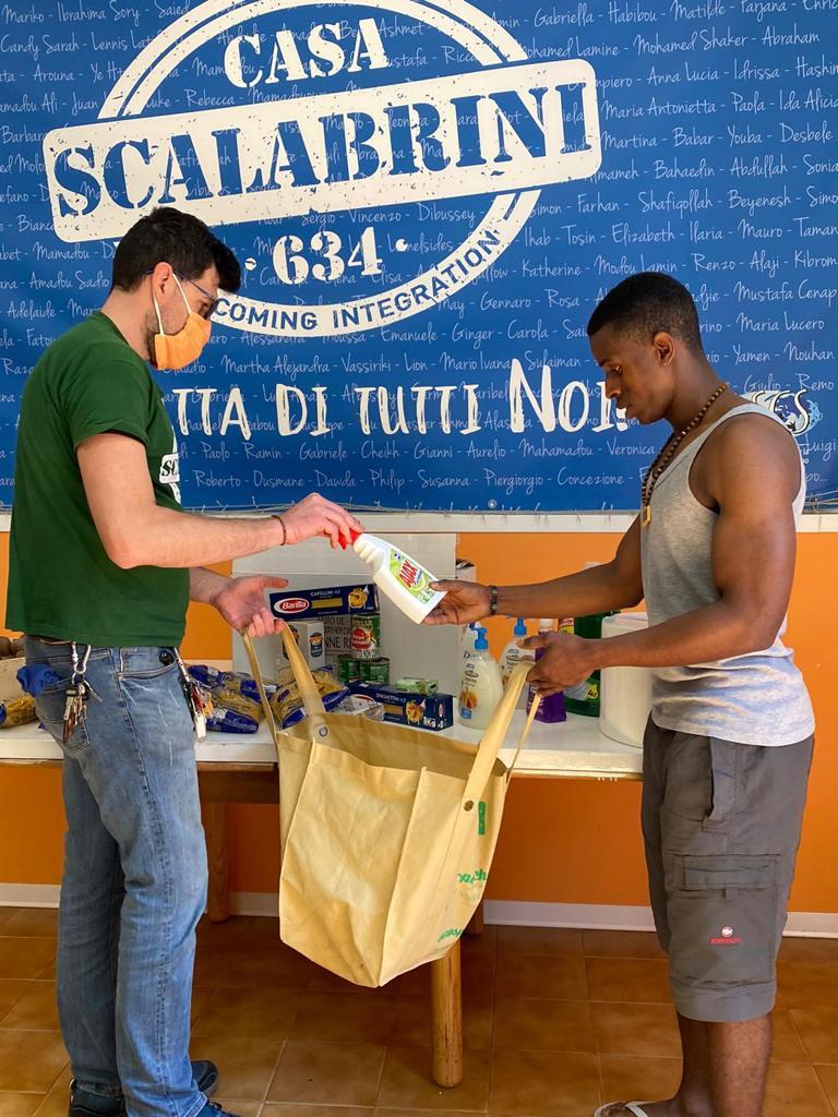 volontario dei missionari Scalabriniani che aiuta un migrante